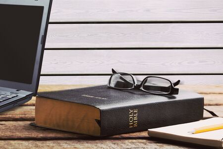 Studiuj czarną księgę Biblii z laptopem, koncepcja religii online