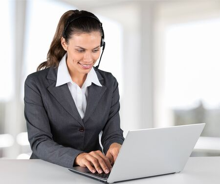 Attractive young woman speaking phone and using laptop