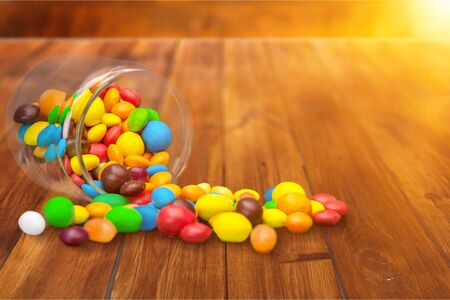 Colorful candies sweets falling out of a glass jar, composition isolated over the white background