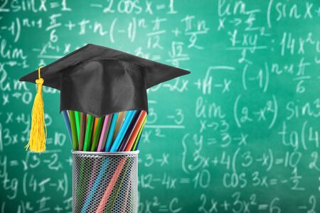 Graduation hat on pencils with formula arithmetic equation graph Archivio Fotografico