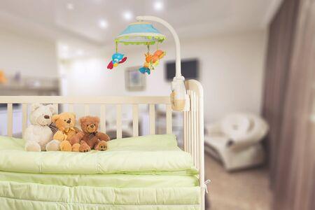 Kinderbett mit Spielzeug im Hintergrund Standard-Bild
