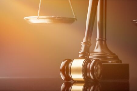 Justice Scales, books and gavel on dark background