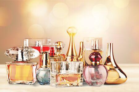 Aromatische Parfümflaschen auf weißem Holzschreibtisch am hölzernen Hintergrund