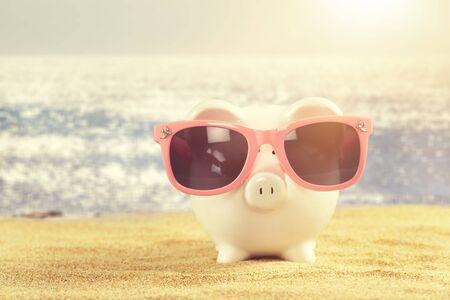 Salvadanaio estivo con occhiali da sole sulla spiaggia Archivio Fotografico