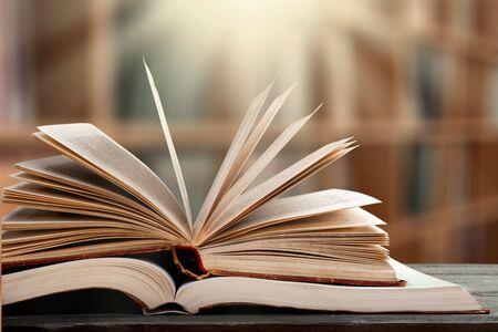 Pila di libri in biblioteca e sfocatura dello sfondo dello scaffale - Immagine Archivio Fotografico