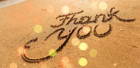 Thank you inscription on sandy sea beach