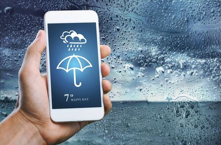 Rainy Day Concept. Hand Holding Smartphone with Weather Information show on Screen. Blurred Traffic Jam and Rain Drops on Glass Window as background Standard-Bild