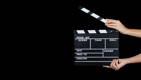 Dos manos que sostienen el uso de la pizarra de claqueta o película en la producción de video, cine, industria del cine sobre fondo negro. - imagen