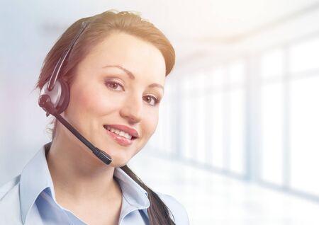 Jeune femme gestionnaire de service téléphonique sur fond de bureau flou Banque d'images