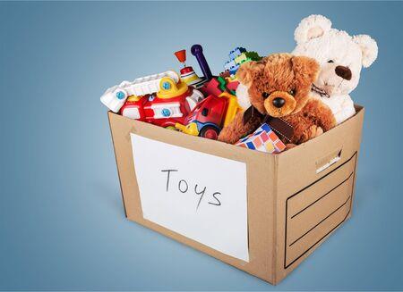 Speelgoedinzameling in doos die op witte achtergrond wordt geïsoleerd