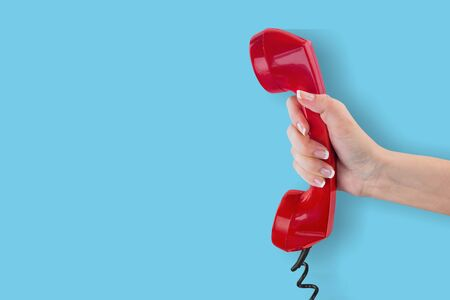 Red telephone receiver on blue background