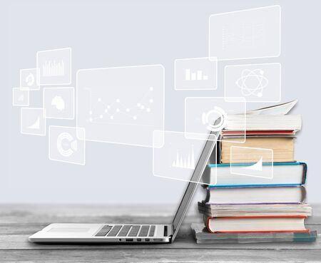 Pila de libros con laptop en la mesa Foto de archivo