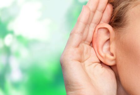 Girl listening with her hand on an ear cose up