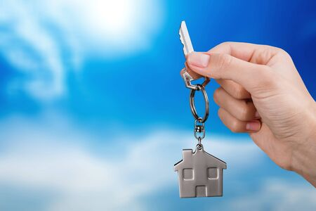 House key in hand on blurred background