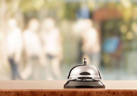 Vintage hotel reception service desk bell on blurred background, bokeh
