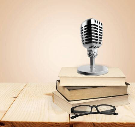 Education teaching concept : Retro microphone with many book put on wooden table isolated on blue background.          - Image 版權商用圖片 - 128244529