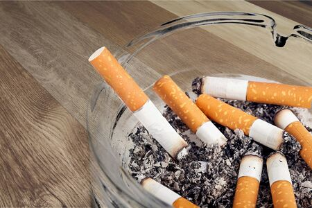 Ashtray and smoked cigarettes on wooden background
