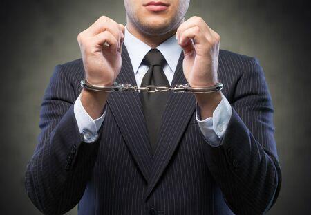 Immagine ritagliata di mani maschili in manette dietro la schiena