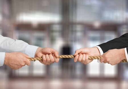 Tug war, two businessmen pulling a rope in opposite directions isolated on naturebackground