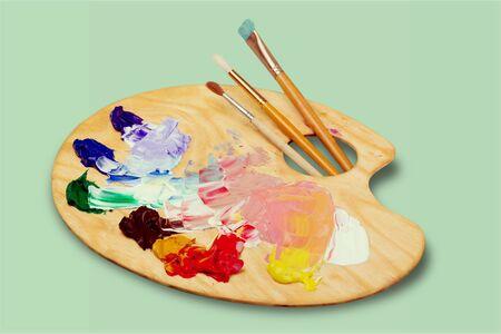 Paleta de arte de madera con manchas de pintura y pinceles sobre fondo blanco.
