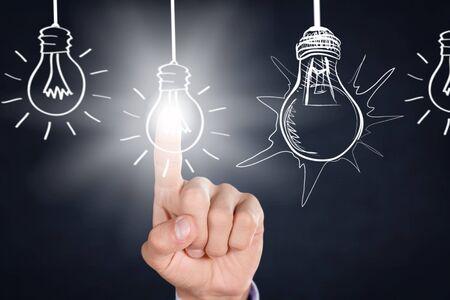 Uomo d'affari che tocca le lampadine bulb