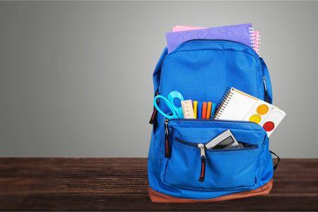 Mochila escolar azul abierta en escritorio de madera Foto de archivo