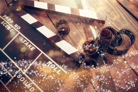 Movie clapper and film reel on a wooden background Reklamní fotografie