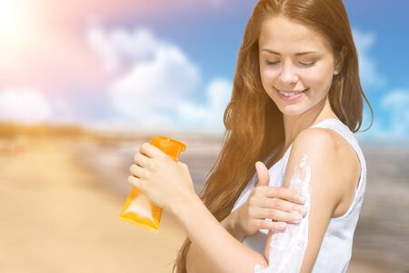 Smiling young woman applying sun block creme on beach
