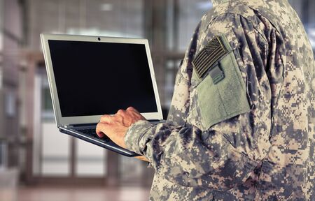 Young military soldier man portrait with laptop on  background