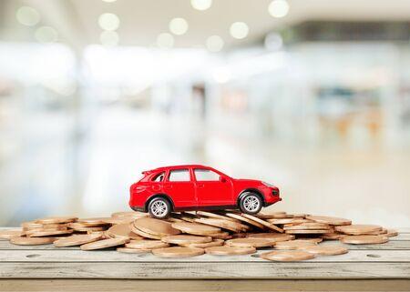 Goldene Münzen und Spielzeugauto im Hintergrund