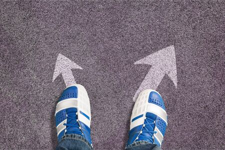 Shoes on the asphalt road with drawn arrow
