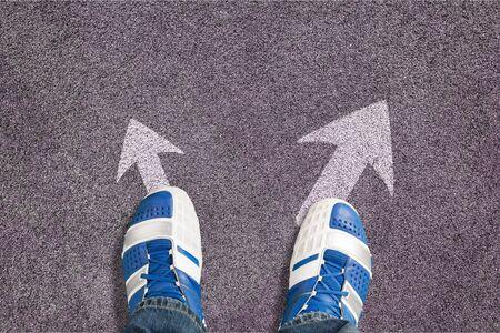 Zapatos en la carretera asfaltada con flecha dibujada