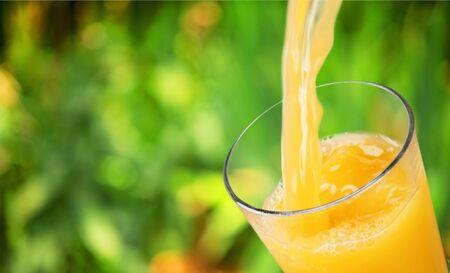 Orangensaft, der in Glas auf Hintergrund gießt Standard-Bild
