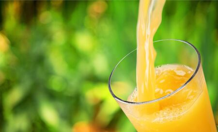 Succo d'arancia che versa in vetro su priorità bassa Archivio Fotografico