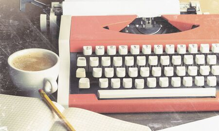 Old typewriter with paper and coffee on background