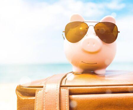 Piggy bank on suitcase on background Banco de Imagens