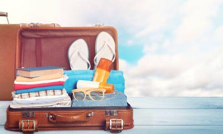Valigia retrò con oggetti da viaggio sullo sfondo del mare