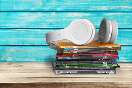 Headphones and compact discs  on wooden background