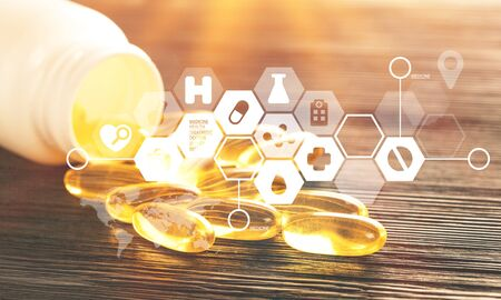 Fish oil capsules with omega 3 and vitamin D in a plastic bottle on a shiny texture with sun beams, healthy diet concept Imagens