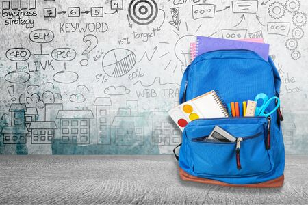 Open blue school backpack on wooden table in classroom background.