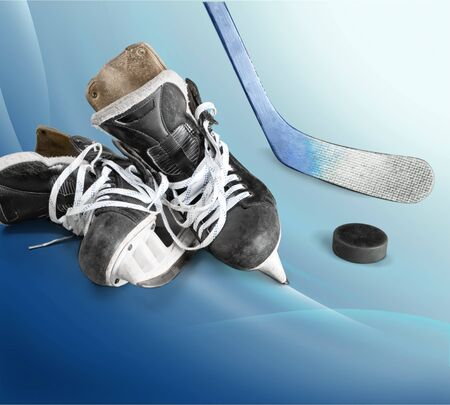 Pair of hockey skates with Hockey stick and puck isolated on white background
