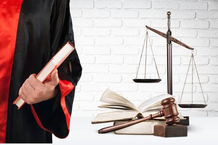 Judge with scale at courtroom, books and wooden gavel