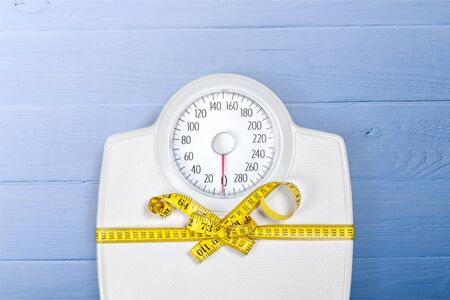 Bathroom scale with a measuring tape isolated on background
