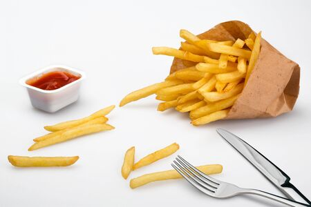 Paper box with pile of appetizing french fries over white planks background Imagens