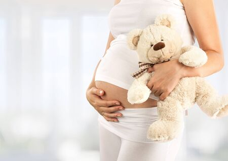 Pregnant young woman keeps the stomach
