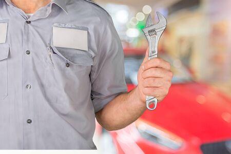 Mecánico de automóviles sonriendo en su garaje