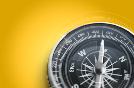 Metal antique compass on yellow background