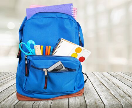 Open blue school backpack on wooden desk and gray background.