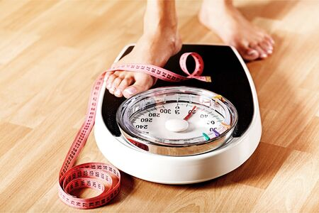 Young woman standing on scales with measuring