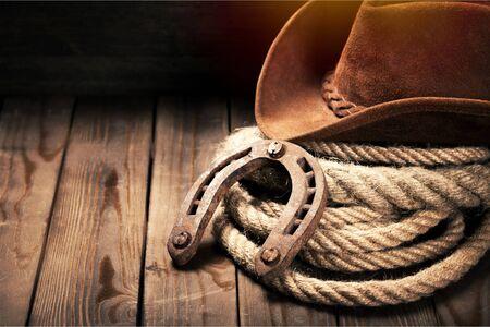 Ferro di cavallo in metallo e cappello da cowboy su legno
